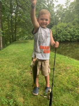 A little boy catches a big mouth bass